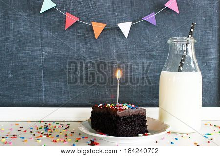 Styled birthday party scene with cake, candle, milk, banner and blank blackboard.