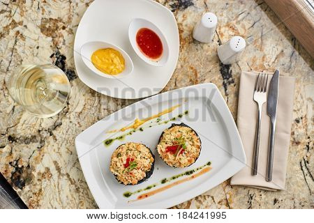 Crab cutlets with mashed potatoes with cuttlefish ink and spicy sauce served on white plate with glass of white wine on marble table