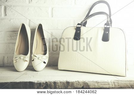 Woman white shoes and bag on brick wall background