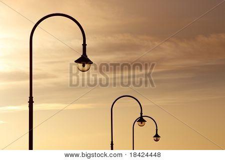 Three street lanterns over the orange sunset sky