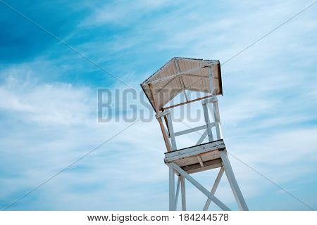 Wooden beach stand on blue sky background ashore of the Mediterranean sea. Sunny day with blue sky and fluffy clouds. Minimalist scene. Location place: Turkey, Kemer.