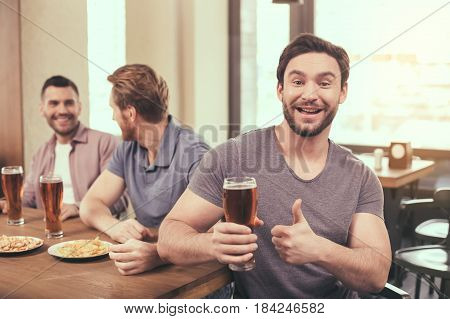 Pizza time. Friends spending time together in restaurant. Guys drinking beer and eating pizza. One man smiling, showing thumb up and looking at camera