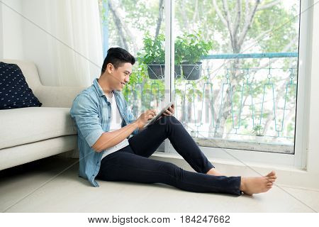 Thoughtful Asian Man Using Smartphone In Bedroom At Home
