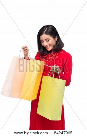 Charming Vietnamese Woman In Red Ao Dai Traditional Dress Holding Shopping Bags.