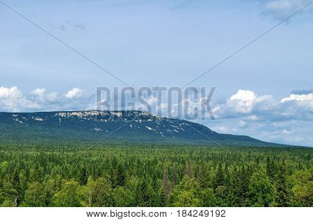 Mountain landscape view of Zyuratkul mountain ridge and mountain summer forest in Southern Urals, Russia - mountain summer forest landscape in cloudy day.Mountain ridge under cloudy sky-view of forest and mountain