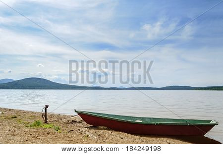 Summer water mountain landscape- Ural mountains on the shore of Zyuratkul Lake, Southern Urals, Russia.Summer landscape view of mountains and lake waters.Summer water mountain background. Summer lake with boat near the water.Mountain summer water view