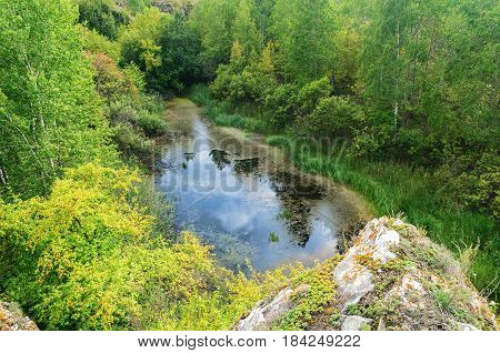 Mountain cliff above the mountain river in summer day -summer landscape. Ustinovskii Canyon in Southern Urals Russia, summer nature of mountain cliff and forest. Mountain cliff in summer  day. Summer mountain background - natural summer mountain landscape