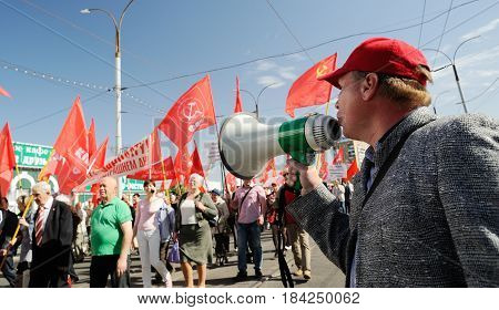 Orel Russia - May 1 2017: May demonstration. Man with loudspeaker talking to crowd with red Communist flags background