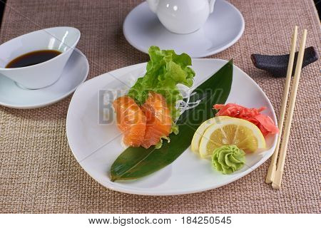Japanese cuisine. Sashimi with fresh salmon served with soy sauce and chopsticks on table.