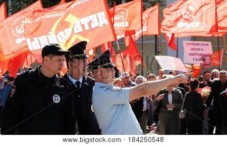 Orel Russia - May 1 2017: May demonstration. Policemen in front of crowd with red Communist flags background