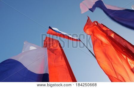 Orel Russia - May 1 2017: May demonstration. Russian tricolor and red Communist flags against clear blue sky