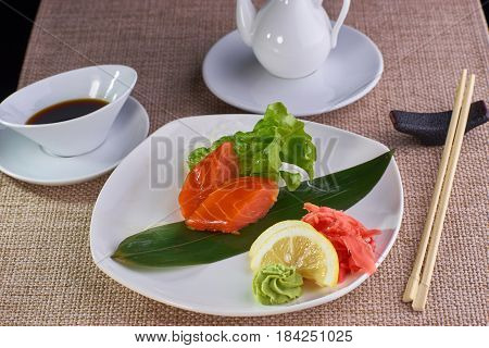 Japanese cuisine. Sashimi with smoked salmon served with soy sauce and chopsticks on table.