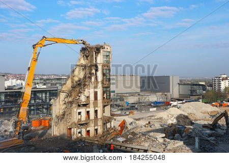 Demolition of a building with a hydraulic excavator in a construction site