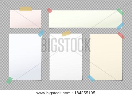 Light blank note, notebook, copybook sheets stuck with colorful sticky tape on squared grey background.