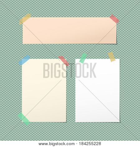 White, brown blank note, notebook, copybook sheets stuck with colorful sticky tape on squared green background.