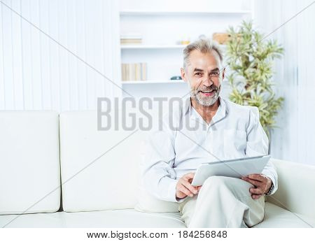 businessman with digital tablet sitting on sofa in bright office. the photo has a empty space for your text