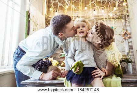happy mother and father kissing their five year old daughter in the living room