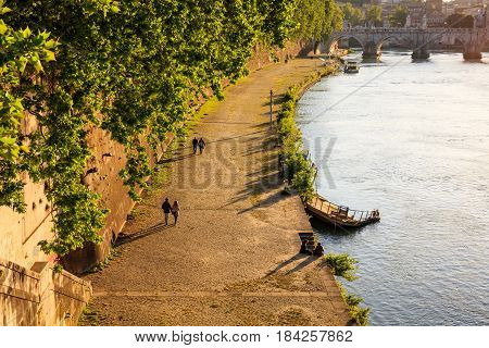 Couples walking by the Tiber river in Rome Italy