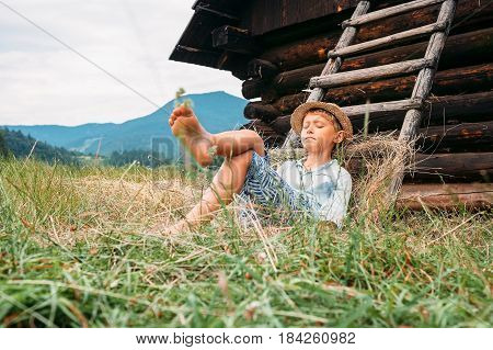 Sleeping country boy lies near the ladder