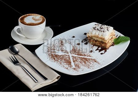 Layered slice of tiramisu cake served on white plate with coffee beans, cocoa crumb and fresh mint leaf, cup of cappucciono coffee, fork and desert spoon