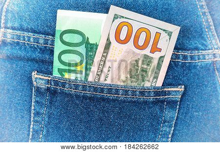 Banknotes of one hundred euro and one hundred american dollars sticking out of the back jeans pocket