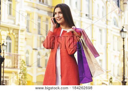 Long Conversation. Portrait Of Attractive And Tender Woman In Red Coat Talking The Phone While Holdi