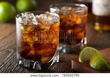 Rum and cola Cuba libre with lime and ice on a wooden bar top.
