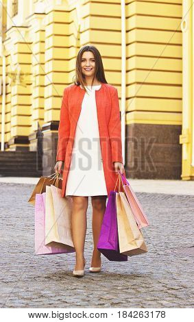Happy Shopping. Beautiful And Young Girl In Red Coat Walking The City With Shopping Bags In The City