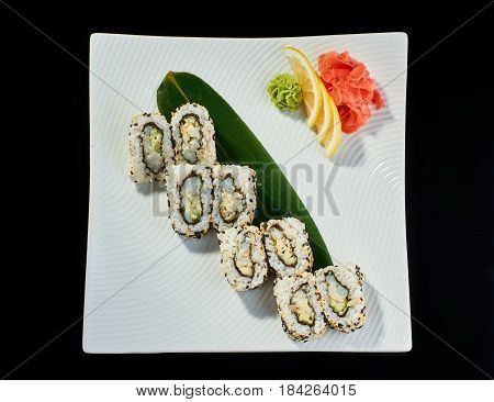 Sushi roll with spicy scallop with vasabi, pickled ginger and lemon slice on white plate on black background