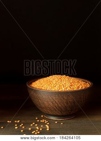 Dried Red Lentils In Bowl On Dark Wooden Background.