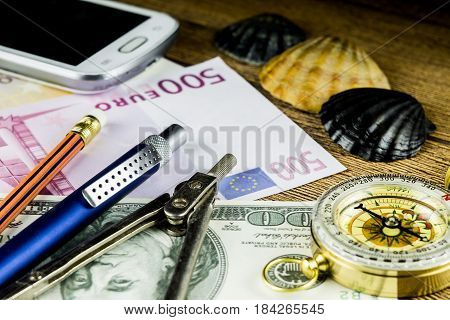 Pensil in travel composition with fotocameramoney and other acsessories on the wooden table