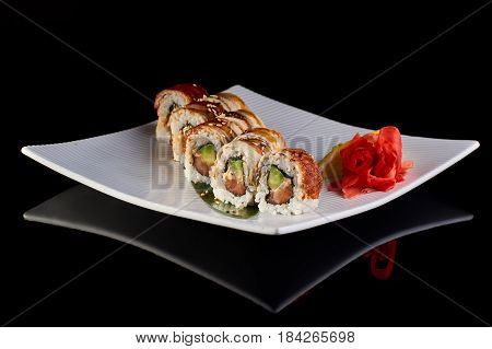Sushi Roll with spicy eel fish, avocado and Philadelphia cheese with vasabi, pickled ginger and lemon slice on white plate on black background