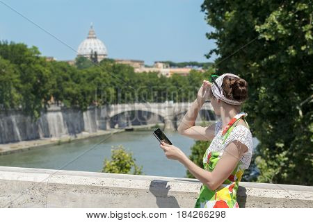 Tourist woman in flower sundress is covering eyes from the sun and holding tablet at Rome bridges and masterpiece dome background