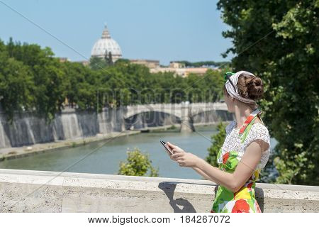 Tourist woman in flower sundress is holding tablet and looking at Rome Tiber bridge and masterpiece dome
