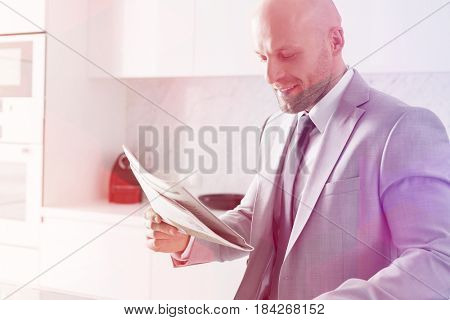 Mid adult businessman reading newspaper in kitchen