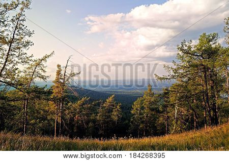 Mountain summer forest landscape -aerial view of summer forest from the Sugomak mountain top in Urals Russia - summer forest mountain background. Warm tones applied.Mountain forest nature -mountain panorama.Summer mountain view.Mountain forest in sunlight