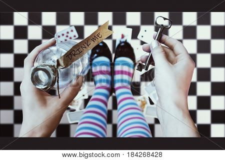 Alice in wonderland. Background. A key and a potion in hands against a  chess floor. 3d illustration