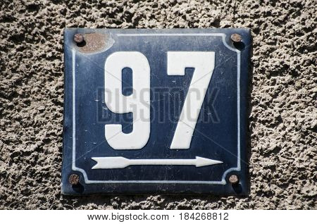 Weathered grunge square metal enameled plate of number of street address with number 97 closeup