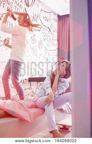 Girl watching sister singing into hairbrush in bedroom