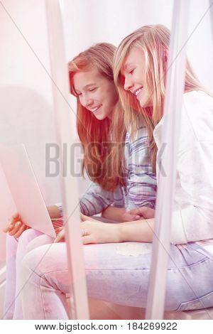 Sisters using laptop on stairway