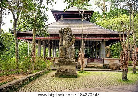 Ancient stone statue of an ancient deity on the island of Bali in a tropical forest among the trees in the background of old houses