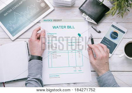 Man holds invoice of water usage over desk with tablet and smartphone with applications made in graphic program.