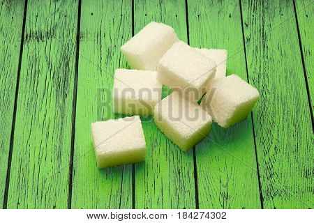 Sugar Cubes On Green Wooden Background