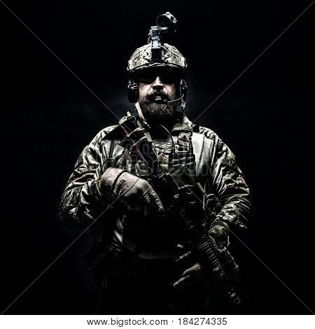 Bearded soldier in Combat Uniforms with weapon, plate carrier and combat helmet are on. Studio shot, dark background. Ruthless and fearless, he brings death to enemies, defending his country