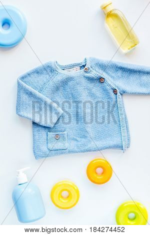 toys and clothes collection for child room on white table background top view