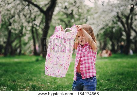cute little toddler girl getting dressed and changing clothes outdoor
