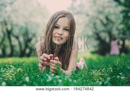 spring closeup outdoor portrait of adorable 11 years old preteen kid girl. Spending spring holidays in beautiful blooming garden