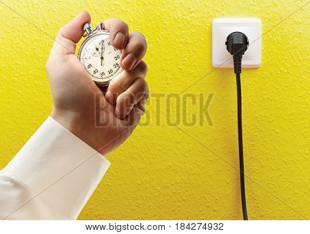 Electric Socket And Stopwatch In Male Hand