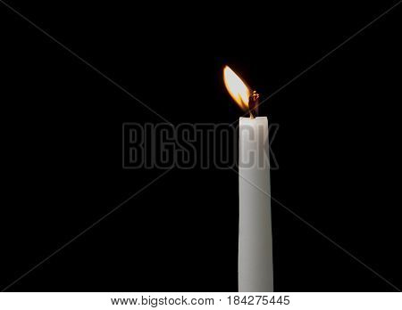 Holy religious white candles burning creating a mysterious atmosphere isolated on a black background with copy space..