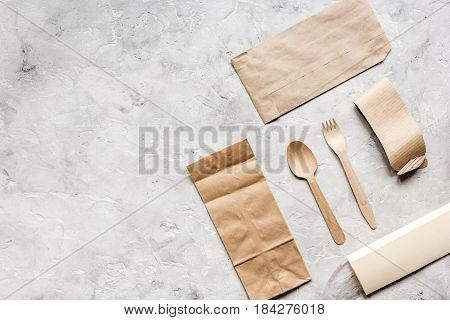 food delivery workdesk with paper bags and flatware on restourant gray table background top view mock-up